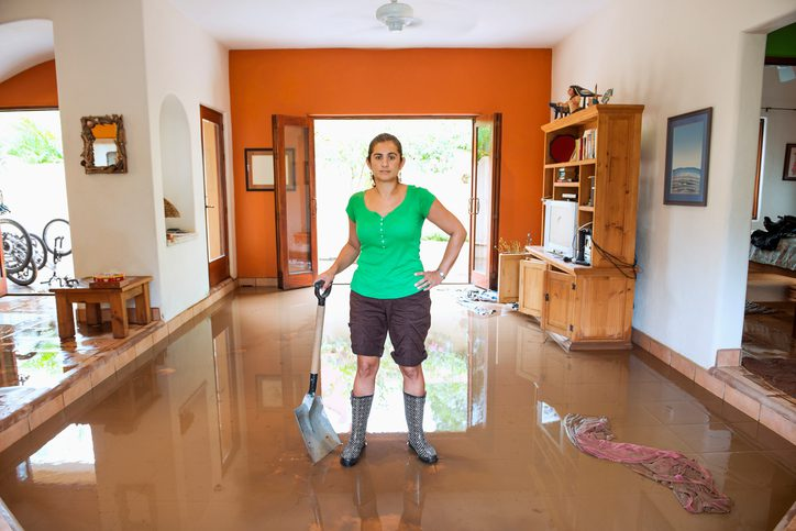 Hispanic woman shoveling water out of flooded house jerome and summey insurance