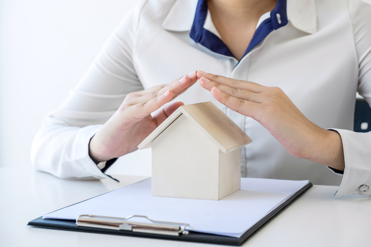 insurance concept - woman with hands over small home model jerome and summey insurance